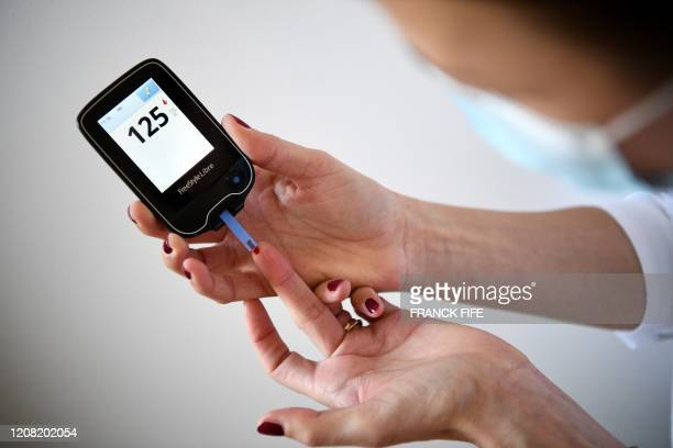 Woman with diabetes uses a glucometer to measure the glycemia in her blood in Paris on March 24 on the eighth day of a strict lockdown in France...