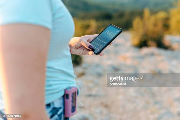woman with diabetes wearing an insulin pump and checking her blood glucose on a smart phone app - diabetes pictures stock pictures, royalty-free photos & images