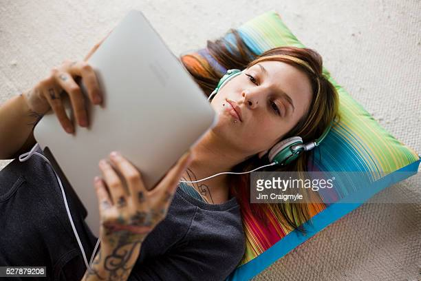 Woman with digital tablet and headphones listening to music