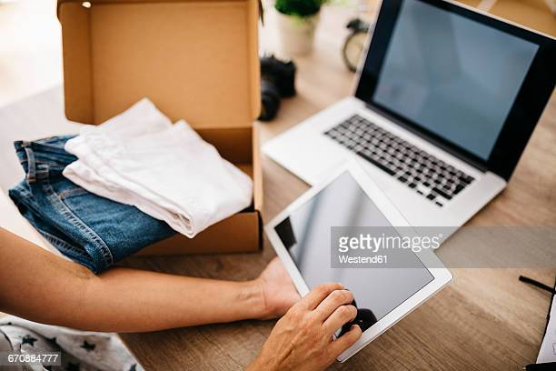 Woman with digital tablet and parcel with clothes
