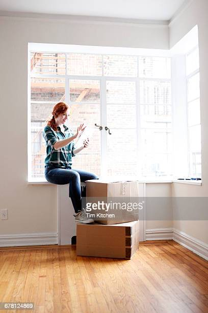 Woman with digital tablet in empty apartment