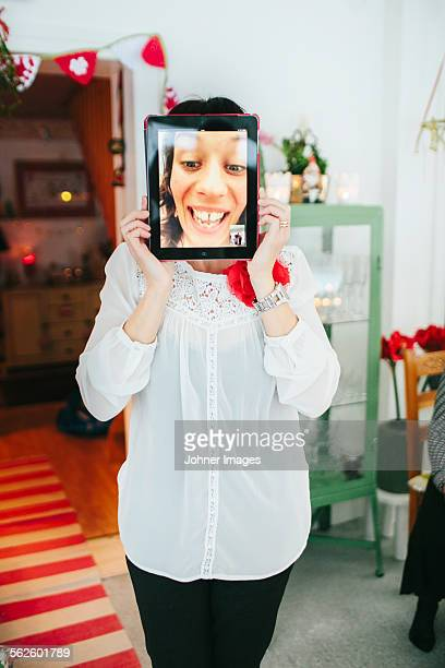 Woman with digital tablet in front of her face