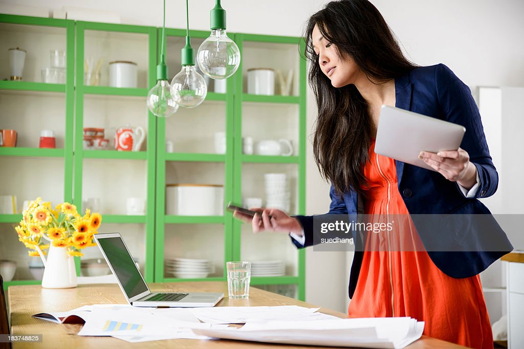 Woman with digital tablet looking at mobile phone : Stock Photo
