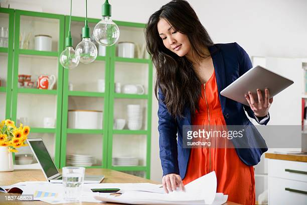 woman with digital tablet looking through paperwork - long bright yellow dress stock pictures, royalty-free photos & images