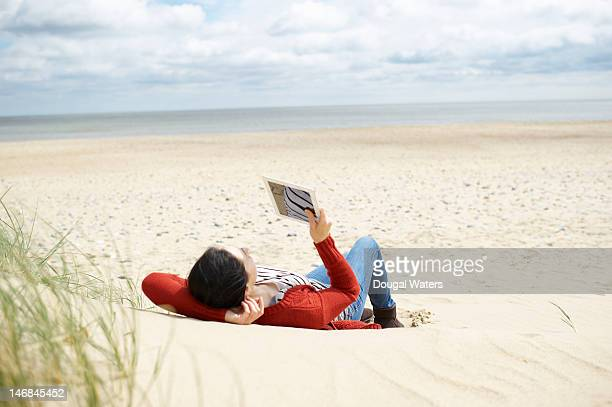 Woman with digital tablet relaxing at beach.