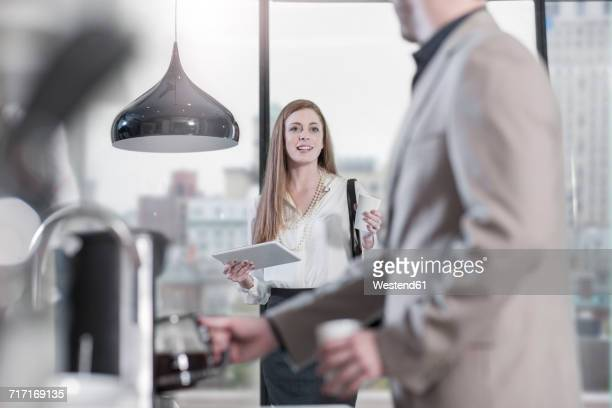 Woman with digital tablet talking to man preparing coffee