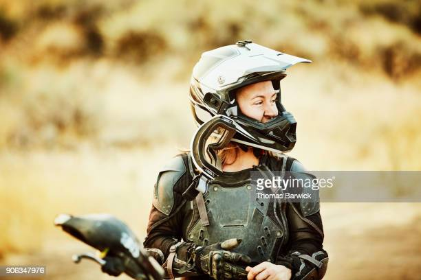 Woman with dirt on face smiling after riding dirt bikes in desert with friends