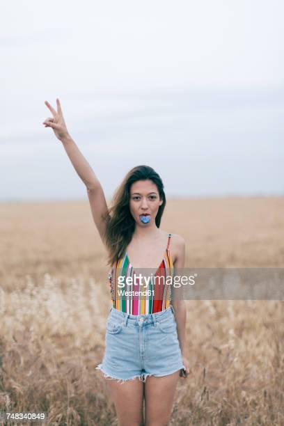 woman with discolored tongue standing in field - aufstand stock-fotos und bilder