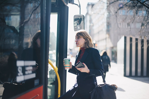 Woman with disposable cup and smart phone standing by bus in city on sunny day - gettyimageskorea
