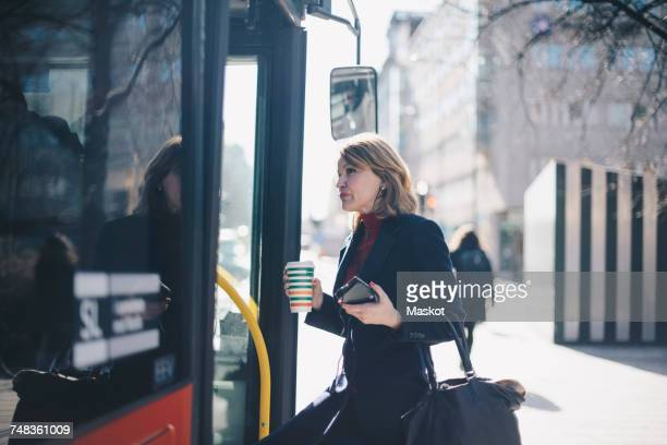 Woman with disposable cup and smart phone standing by bus in city on sunny day