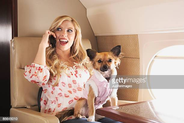 Woman with dog and cell phone on private airplane