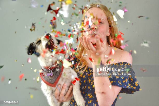 Woman With Dog Blowing Confetti Against Gray Background