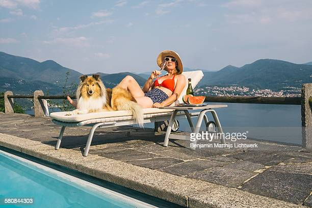 Woman with dog enjoying champagne by the pool
