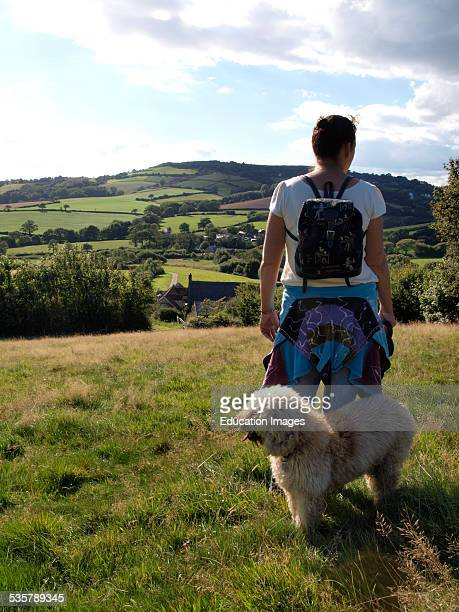 Woman with dog looking at view of Dorset countryside, Chideock, Dorset, UK.
