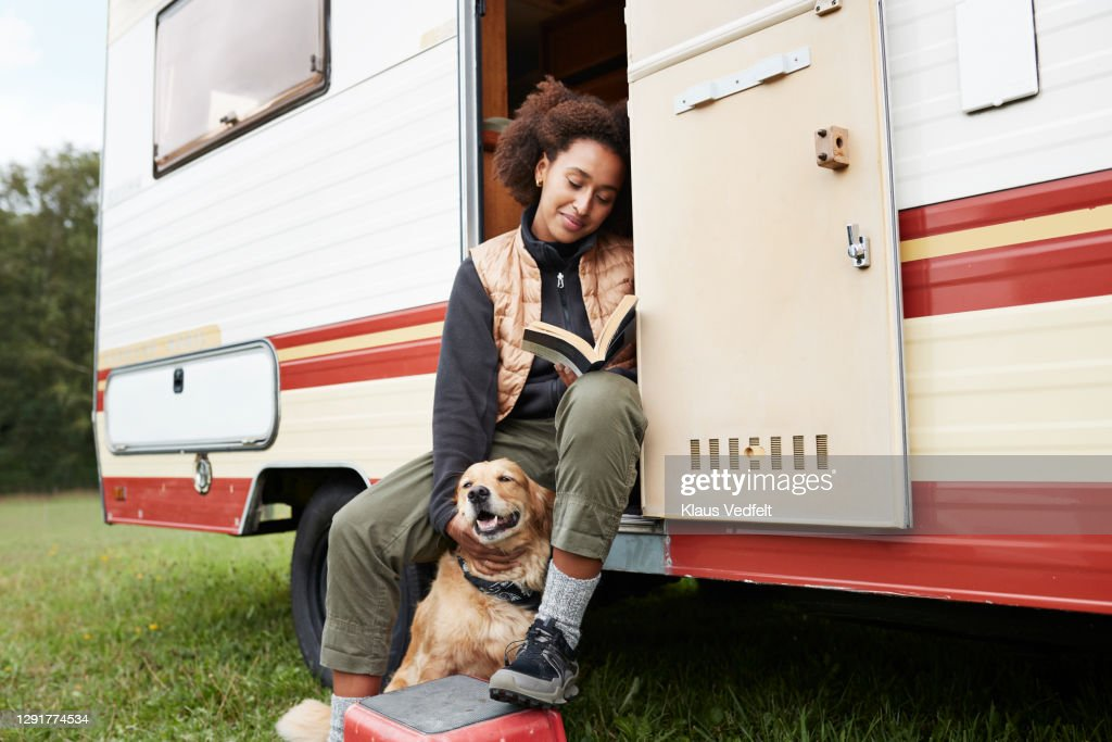 Woman with dog reading book in motor van : Stockfoto