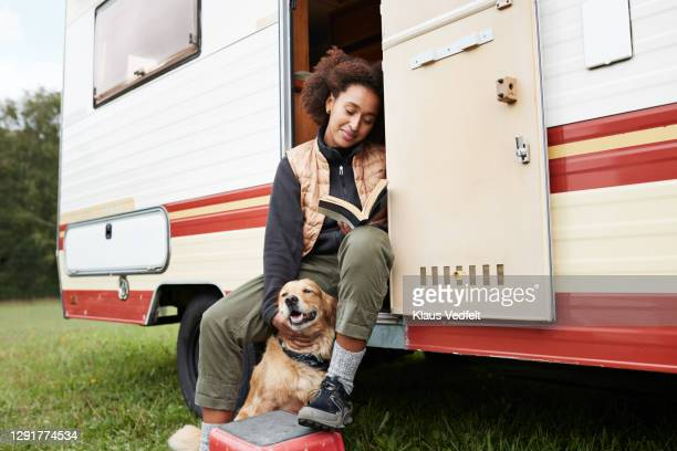 woman with dog reading book in motor van - animal stock pictures, royalty-free photos & images