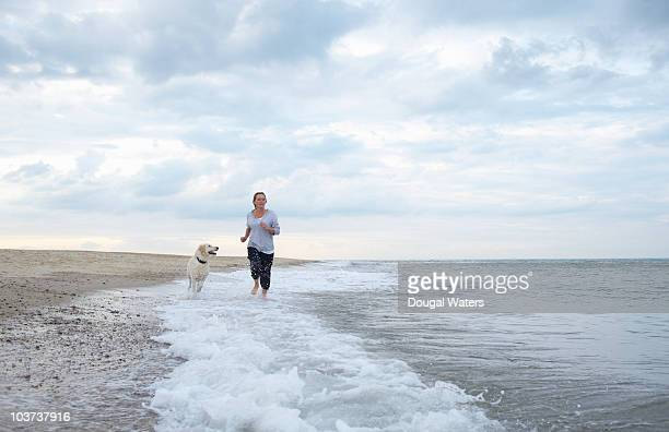 woman with dog running along beach. - 45 49 years stock pictures, royalty-free photos & images