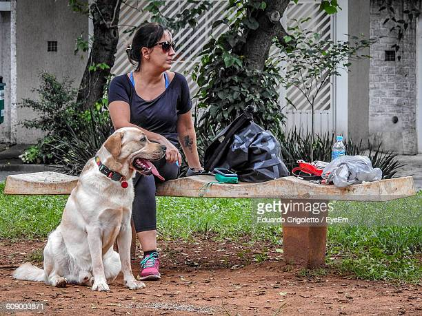 Woman With Dog Sitting On Bench At Park