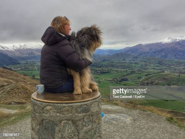 woman with dog sitting on built structure while looking at scenic mountains against sky - arrowtown stock pictures, royalty-free photos & images