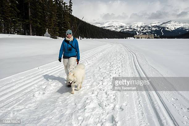 Woman with dog walking on frozen lake Louise
