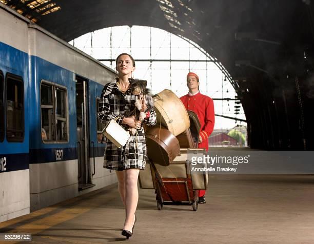 Woman with dog walking on train platform.
