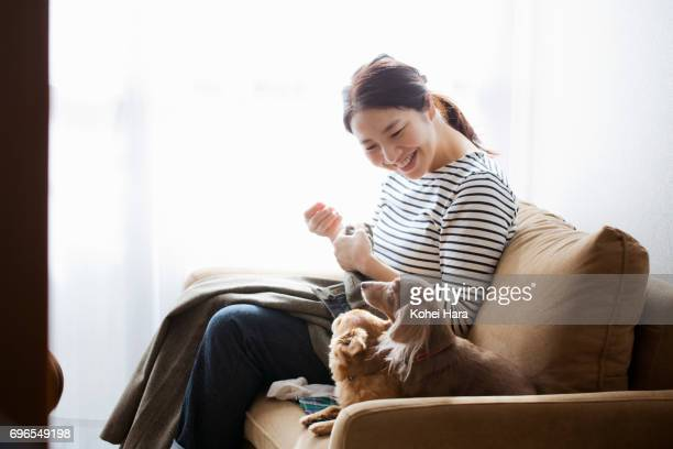Woman with dogs sewing on the sofa