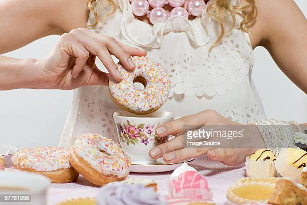 woman with doughnut and cup of tea - over eating stock pictures, royalty-free photos & images