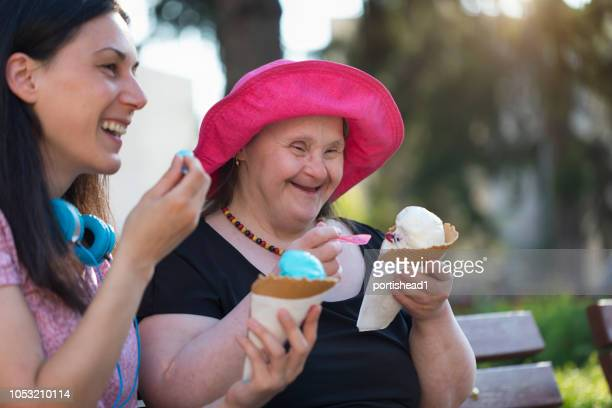 woman with down syndrome and her friend eating ice cream and having fun - down syndrome stock pictures, royalty-free photos & images
