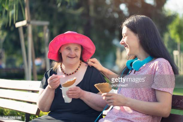 woman with down syndrome and her friend eating ice cream and having fun - persons with disabilities stock pictures, royalty-free photos & images