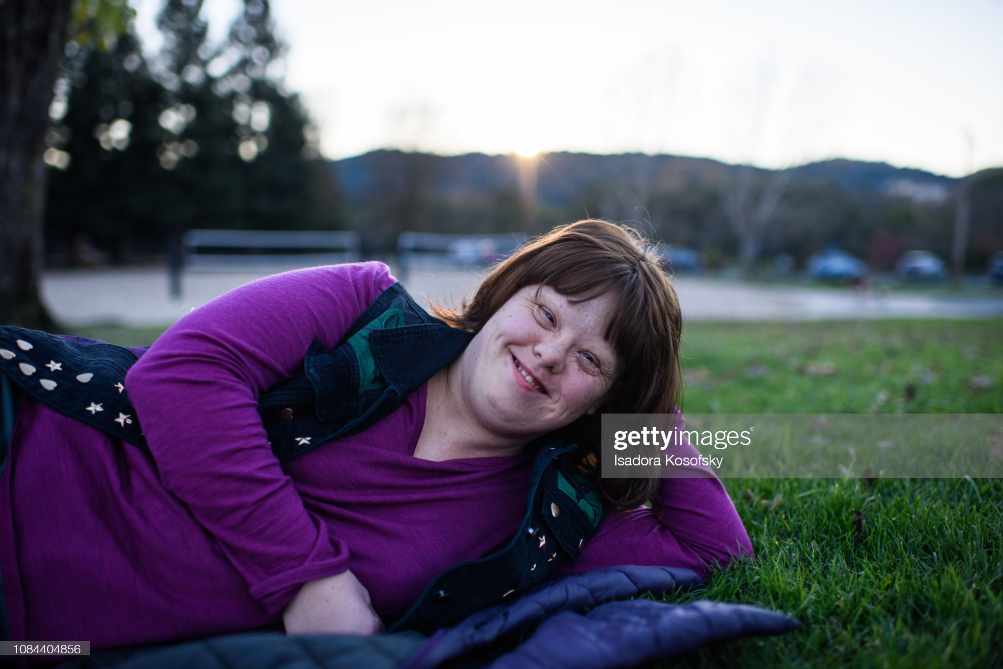 Woman with Down Syndrome relaxes outside. : Stock Photo