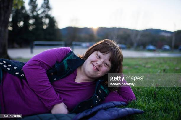 Woman with Down Syndrome relaxes outside.