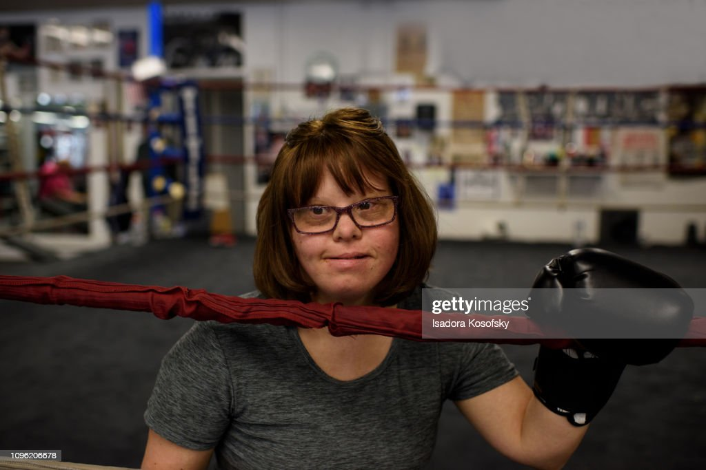 Woman with Down Syndrome sits in boxing ring. : Stock Photo