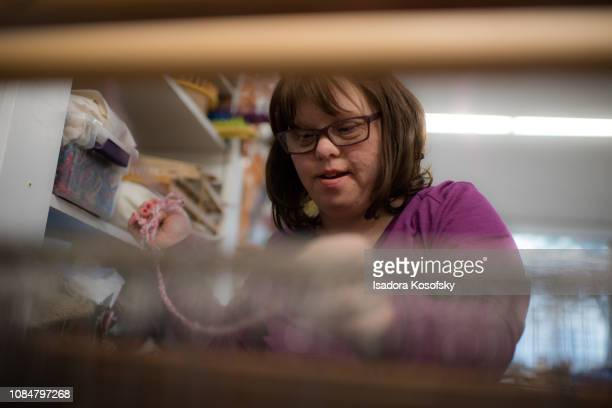 Woman with Down Syndrome weaves at a loom.