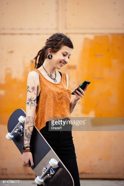 Woman with dreadlocks holding skateboard and texting