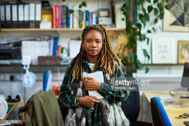 woman with dreadlocks standing in office, looking at camera - locs hairstyle stock pictures, royalty-free photos & images