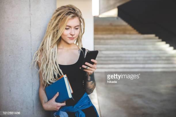 frau mit dreadlocks mit telefon an der universität - blondes haar stock-fotos und bilder