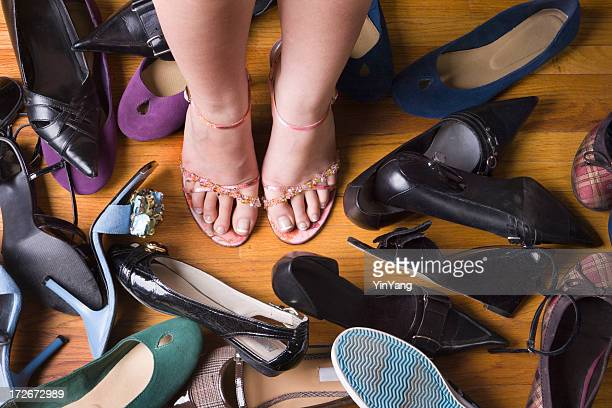 woman with dress shoes, making choices from large footwear variety - fetish wear stock photos and pictures