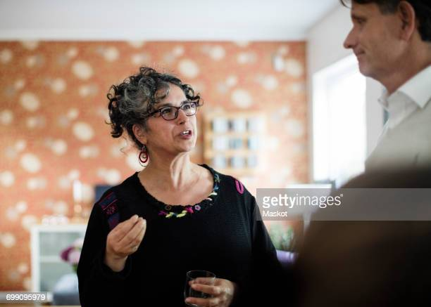 woman with drink gesturing while talking to man at home - fugitive stock photos and pictures
