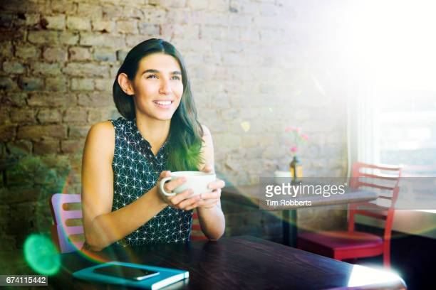 woman with drink looking forward in coffee shop - coffee drink stock pictures, royalty-free photos & images