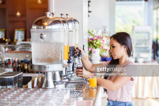 woman with drink standing in coffee shop - coffee drink stock pictures, royalty-free photos & images