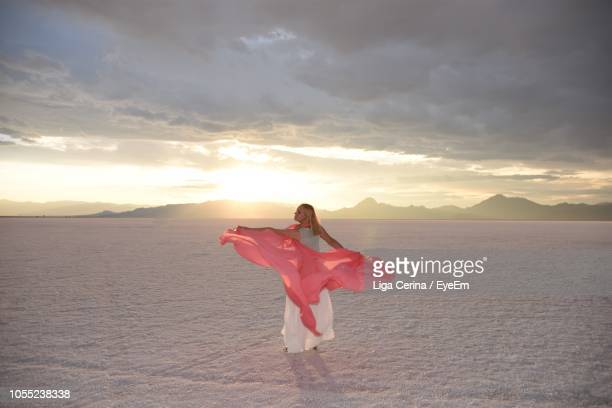 woman with dupatta standing on desert against cloudy sky - dupatta stock pictures, royalty-free photos & images
