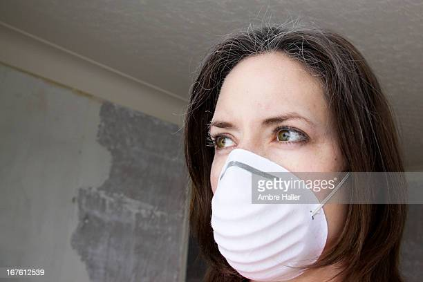 Woman with dust mask on and white dust in her hair