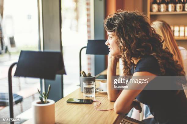 Woman with earphones and smart phone in cafe