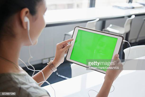 Woman with earphones in looking at green screen on tablet