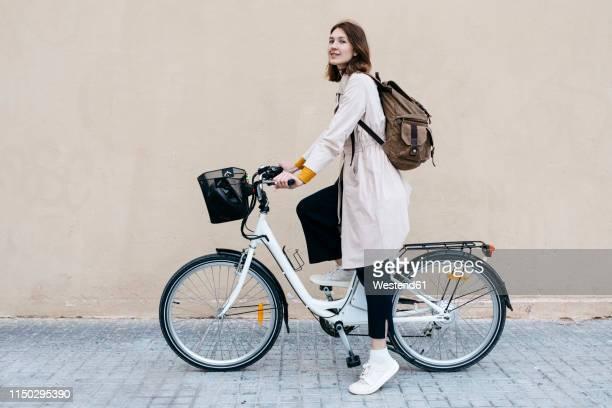 woman with e-bike at a wall - andar en bicicleta fotografías e imágenes de stock