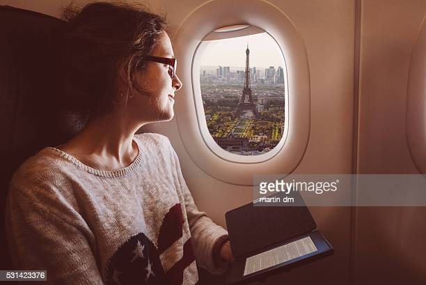 Woman with e-book in the airplane travelling to Paris