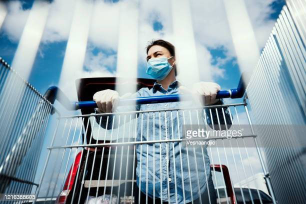 woman with empty shopping cart wearing protective surgical masks and gloves - merchandise stock pictures, royalty-free photos & images