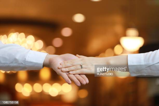 Woman with engagement ring holding man hand