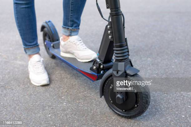 woman with e-scooter, partial view - electric scooter stock pictures, royalty-free photos & images