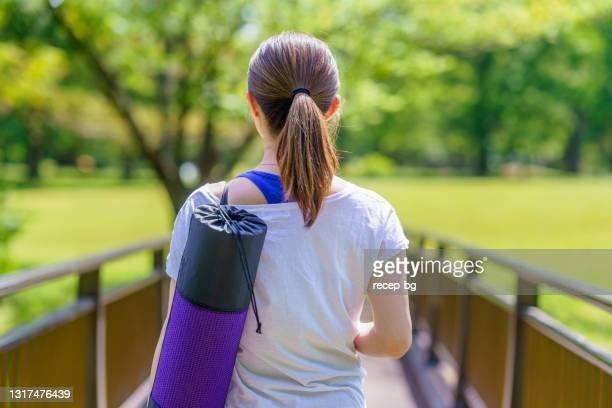 自然の中を歩く運動マットを持つ女性 - エクササイズマット ストックフォトと画像